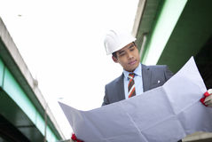 Highway construction contractor. Asian young architect cheking plan on highway construction site Royalty Free Stock Images