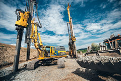 Highway construction with heavy duty machinery. Two Rotary drills, bulldozer and excavator working. Highway construction site with heavy duty machinery. Two Royalty Free Stock Photos