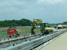 Highway construction machinery Oklahoma. Heavy machinery at work in the median on Oklahoma Interstate 40. Road construction with trucks, a bucket and other Royalty Free Stock Image