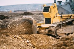 Highway construction site close up with industrial machinery, excavator and bulldozer working Royalty Free Stock Images