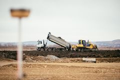 Highway construction site development with dumper truck dumping earth and bulldozer leveling and pushing earth. Construction site development with dumper truck Stock Photos
