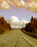Highway in countryside. Scenic view of highway receding through Autumnal forest in countryside under cloudscape Stock Photography