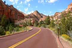 A highway curves through a beautiful landscape of canyons and red rock mountain peaks stock images