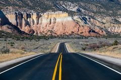 Highway curving into the distance toward colorful cliffs stock photography