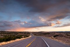 Highway curving into the distance through the landscape near Santa Fe, New Mexico underneath a dramatic colorful sky at sunset stock photography