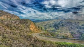 Highway curving through the mountain highlands. Stormy skies. royalty free stock images