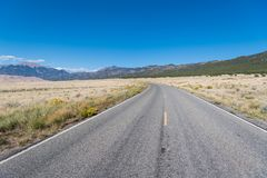 Highway curving to perspective through grassy plains underneath a perfect blue sky towards the Rocky Mountains. Highway entering Great Sand Dunes National Park royalty free stock photo