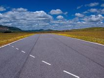 Highway cut (horizontal). Rare highway cut in the middle of the field under blue sky with clouds stock photography