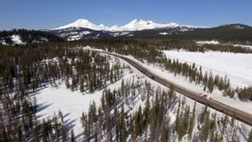 Highway Cuts Through The Cascade Mountains Central Oregon. Winter has set in near Three Sisters and Broken Top Mountains in Oregon Stock Image