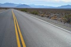 Highway in Death Valley desert blue mountain range Stock Photo