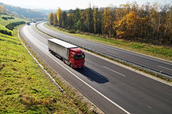 The highway between deciduous forests with leaves in fall colors, the highway ride three trucks. View from above Royalty Free Stock Images
