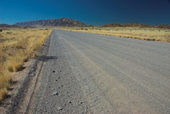 Highway in desert. Scenic view of highway receding through Namibian desert with mountains in background Stock Images