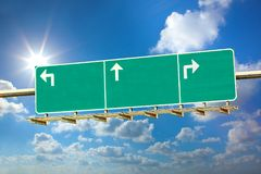 Highway direction sign. Highway blank sign with tree directions on sunny blue sky background royalty free stock image