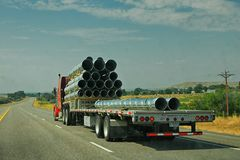 Truck hauling pipe down the highway. With the highway disappearing into the distance, a truck chugs down it with a load of shiny metal pipe trailing behind it Stock Photos