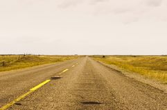 Highway dissappearing to a vanishing point. Highway 41 near St. Lazare travelling past golden fields toward a vanishing point on the distant horizon Stock Image