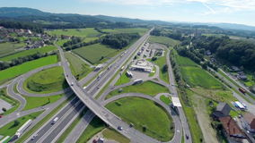 Highway exit near a town. Aerial shoot of a highway turn exit spin around to come to the town stock video footage