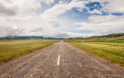 The highway extends. Beyond the horizon between the mountain ranges stock images