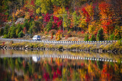 Highway through fall forest. Camper driving though fall forest with colorful autumn leaves reflecting in lake. Highway 60 at Lake of Two Rivers, Algonquin Park Royalty Free Stock Photography