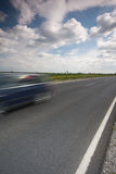 Highway with a fast car. Highway with a fast moving car Royalty Free Stock Image