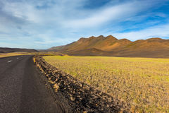 Highway through Iceland field landscape under a blue summer sky. Stock Photography