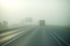 The highway in the fog. The truck rides ahead Stock Photo