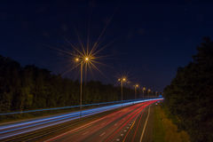Highway through a forest at night. Dutch highway (E30/A28) at night, nearby Utrecht. The picture is taken with a long Exposures and a small aperture Royalty Free Stock Images