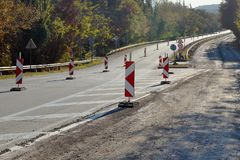 Highway in the forest during repair on an autumn day: half of the road is blocked, warning signs are installed royalty free stock images
