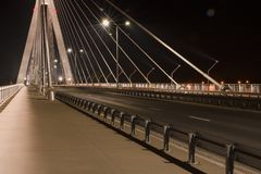 Highway going through a cable-stayed bridge. With big steel cables, close-up in the night stock photo