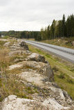 Highway among granite rocks in early autumn. Royalty Free Stock Images