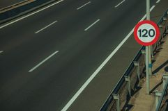 Highway with heavy traffic and SPEED LIMIT signs in Madrid. Empty multi lane highway and lonely SPEED LIMIT signpost at the roadside with guard rail, on sunset royalty free stock photography