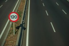 Highway with heavy traffic and SPEED LIMIT signs in Madrid. Empty multi lane highway and lonely SPEED LIMIT signpost at the roadside with guard rail, on sunset royalty free stock images
