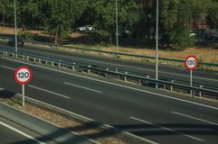 Highway with heavy traffic and SPEED LIMIT signs in Madrid. Empty multi lane highway and two SPEED LIMIT signposts at the roadside with guard rail, on sunset in stock photos