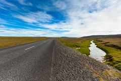 Highway through Icelandic landscape under a blue summer sky with Stock Image