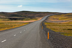 Highway through Icelandic landscape under a blue summer sky Stock Photos