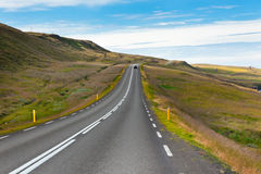Highway through Icelandic landscape under a blue summer sky. Stock Photo