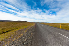 Highway through Icelandic landscape under a blue summer sky with Stock Photos