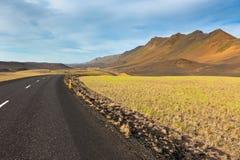 Highway through lava field landscape under a blue summer sky Stock Photos