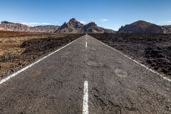 Highway through a lava field. Scenic view of a highway receding through a lava field on Tenerife, Canary Islands, Spain Stock Photography