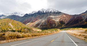 Highway Leads Through Peaks Alaska Range Fall Autumn Season. The sun peeps through a partly cloudy sky to light the Alaska Range Royalty Free Stock Images