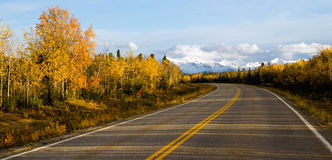 Highway Leads Through Peaks Alaska Range Fall Autumn Season. The sun peeps through a partly cloudy sky to light the Alaska Range Stock Image