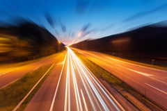 Highway with light trails at dusk in blurred motion Stock Photo