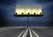 Highway with lighted blank billboard and evening sky Stock Photos