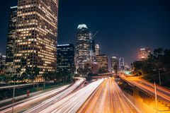 Highway in Los Angeles at night. Snow covered  highway in Los Angeles at night with illuminated skyscrapers along the left  next to the sidewalk Royalty Free Stock Images