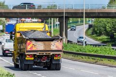 Highway maintenance tipper lorry truck on uk motorway in fast motion stock photography