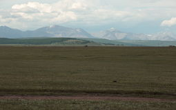 Highway and the Mongolian steppe on a background of mountains of the Eastern Sayan. The surrounding steppe near the village of Turt at the Northern border of Stock Photos
