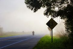 Highway in the morning fog, with motorcycle stock image