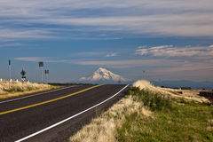 Highway and Mount Hood. Scenic view of highway receding towards Mount Hood in distance under cloudscape, Oregon, U.S.A Royalty Free Stock Photos