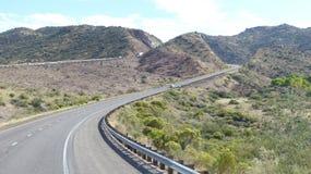 Highway in mountainous desert landscape Stock Photo