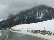 Highway in mountains. Wet highway in mountains in winter season beside old house royalty free stock photography