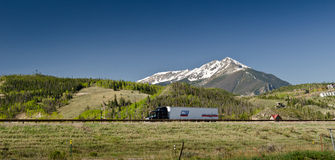 Highway and mountains in the background. Heavy truck going on a highway in Colorado, USA stock photography